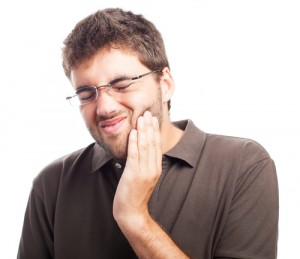man suffering tooth pain on a white background