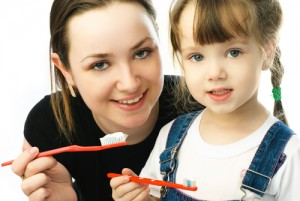mother teaching her daughter brushing teeth