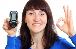 Smiling woman with glucose meter